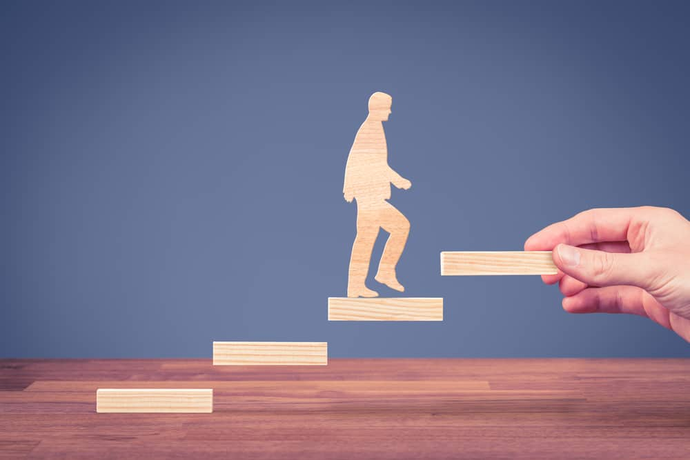 Een houten figuur gaat stap voor stap verder in zijn carrière, net als jij met Loopbaanexpert