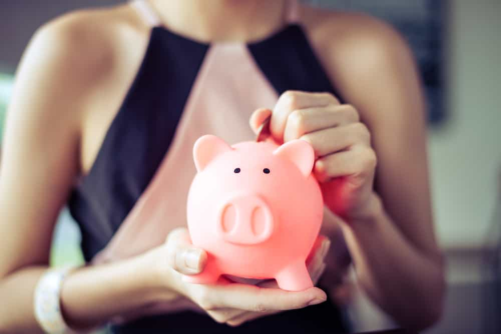 Vrouw met spaarvarken in de hand want bij een carrièreswitch kan je best je geld in de gaten houden.