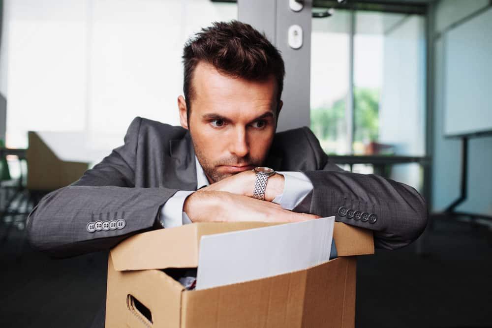 Man met kartonnen doos na ontslag. Hoe kan je een job vinden die bij je past? – loopbaanexpert