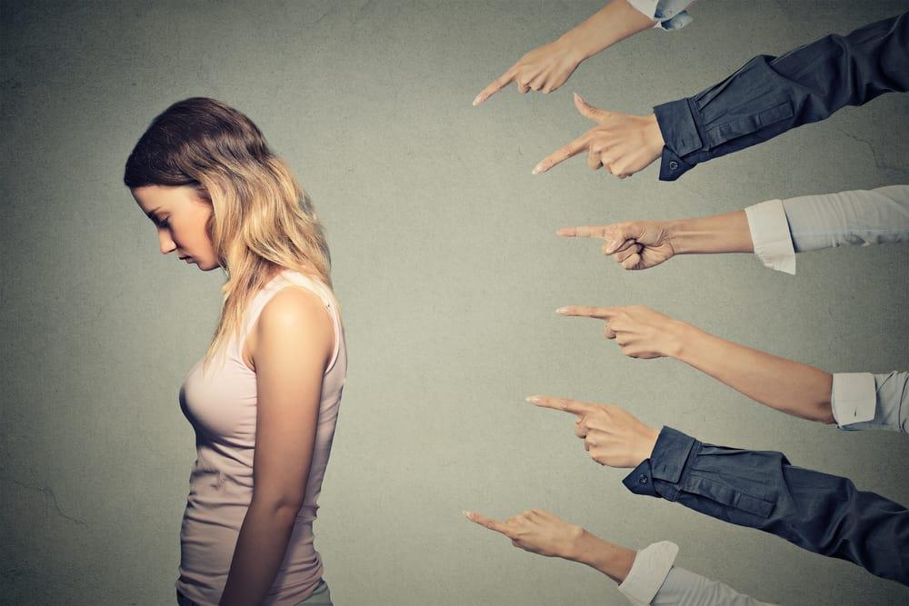 6 mensen wijzen naar een jonge vrouw. Een loopbaancoach van Loopbaanexpert helpt bij pesten op het werk.