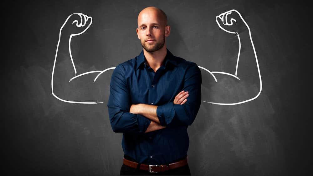 Man tegen krijtbord waar gespierde armen op getekend zijn. Loopbaanexpert over de kracht van loopbaanbegeleiding.