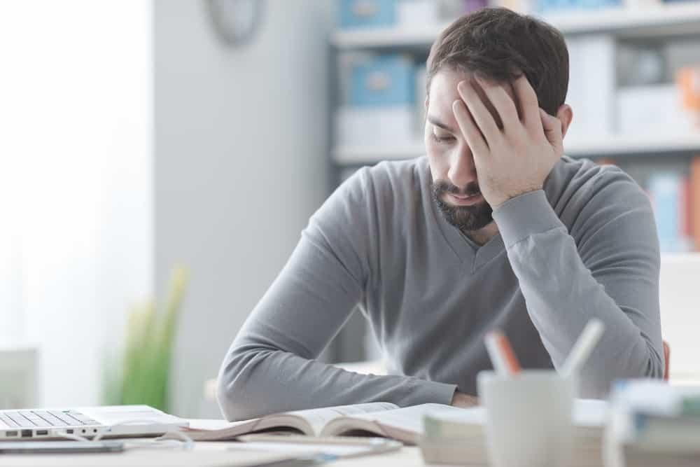 Verveelde man zit aan bureau en kan loopbaanbegeleiding gebruiken - Loopbaanexpert